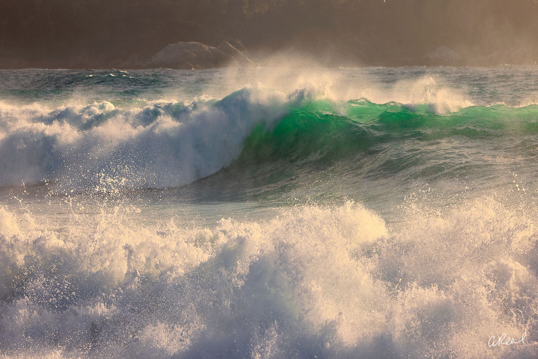 A crashing emerald wave with warm highlights in Pebble Beach, California titled Emerald Crush by photographer Aaron Reed.
