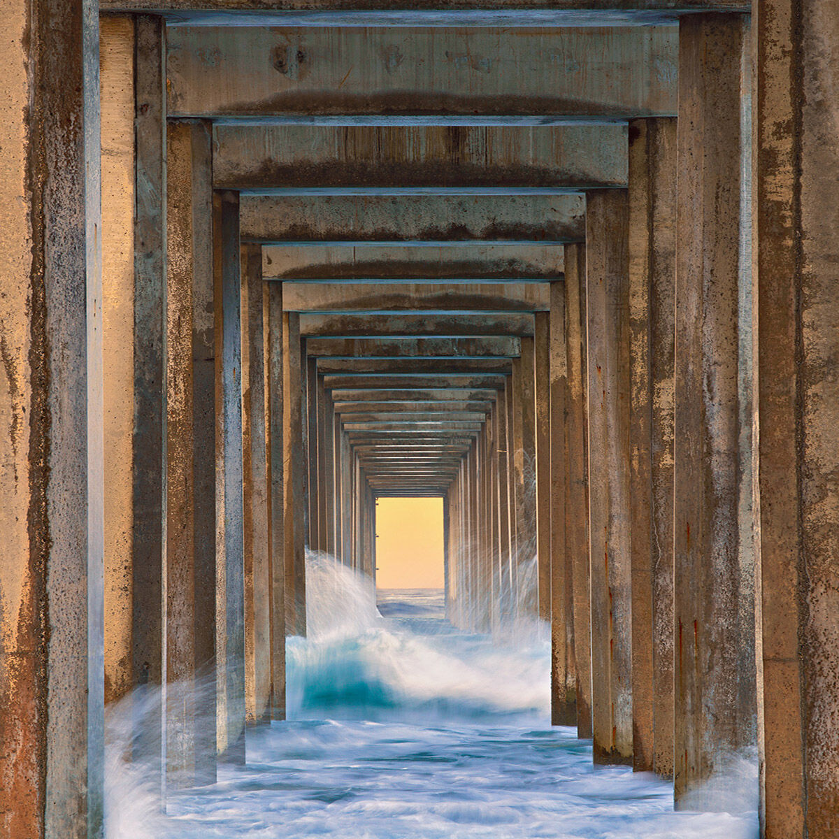 A fine art photograph of crashing waves under the Scripps Pier in La Jolla, California titled Ebb & Flow.