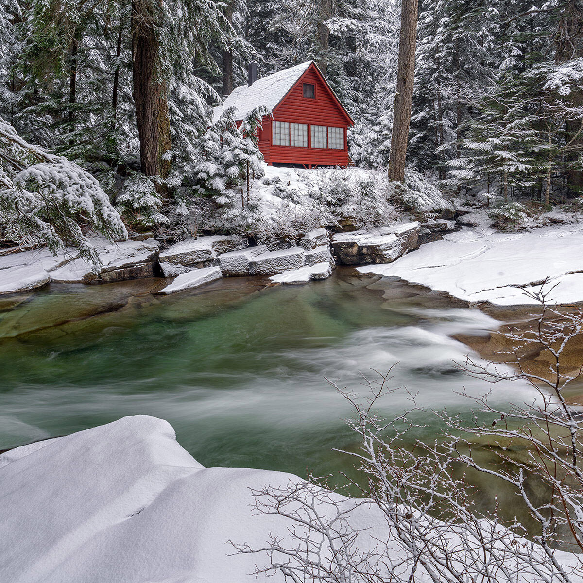 A fine art photograph of a red cabin in the woods next to Denny Creek on Snoqualmie Pass in Washington State.