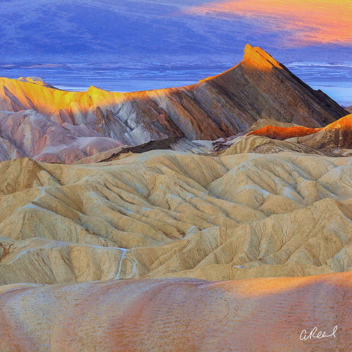 A fine art photograph of Zabriskie Point in California titled First Strike.